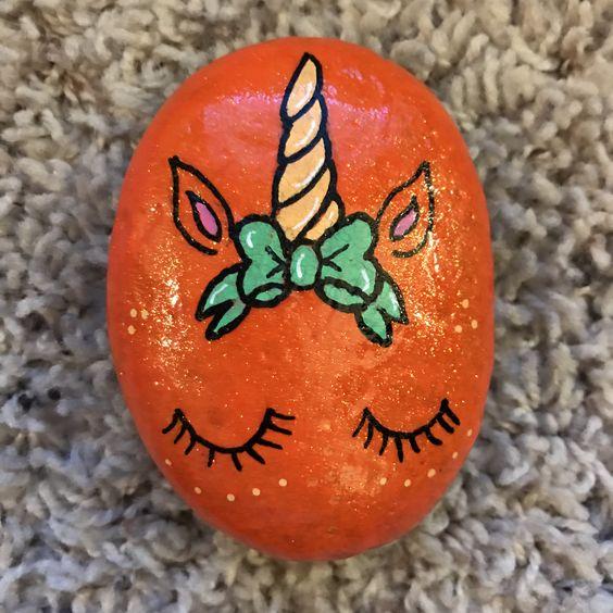Orange unicorn face painted rock